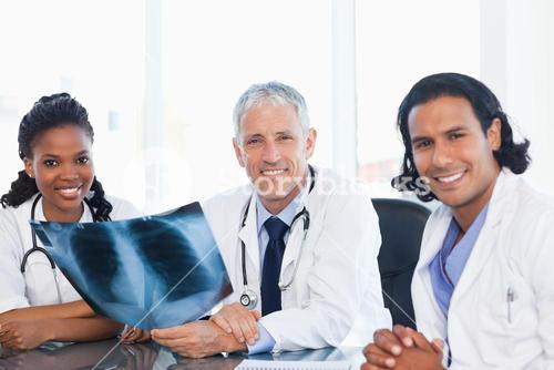Medical team smiling while working on a patients xray