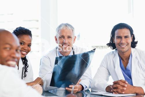 Mature doctor surrounded by three colleagues holding an xray of lungs