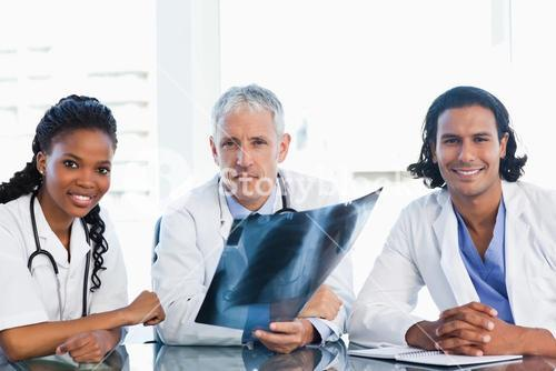 Serious doctor with smiling coworkers looking at an x-ray scan of lungs