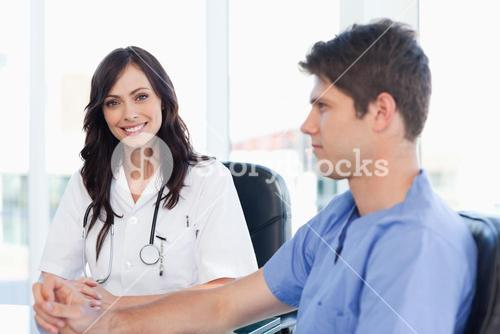 Young nurse sitting at the desk looking at her coworker