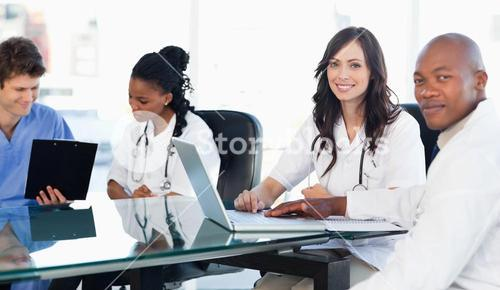 Two members of a medical team looking at the camera while working on a laptop