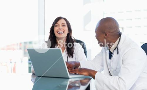 Nurse laughing while working on a laptop with a colleague