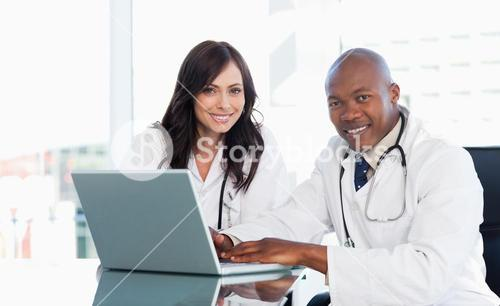 Smiling medical staff working in front of a laptop while sitting at the desk