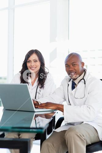 Smiling doctor working on a laptop while accompanied by his colleague