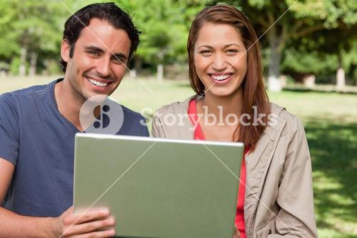 Two smiling friends looking ahead as they hold a tablet