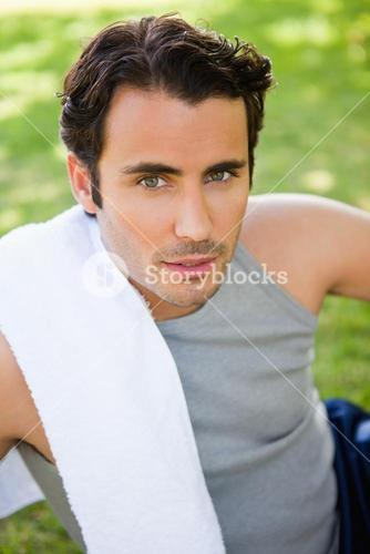 Man looking upwards with a towel resting on his shoulder