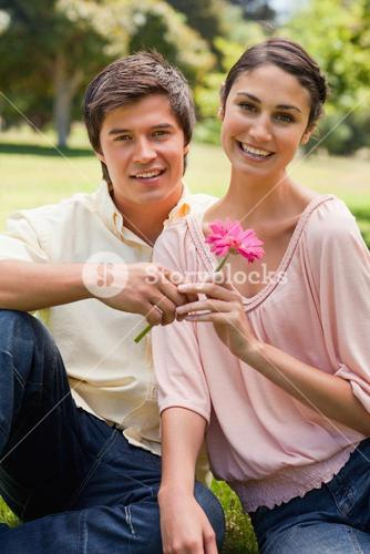 Man giving a flower to a woman as they both look ahead