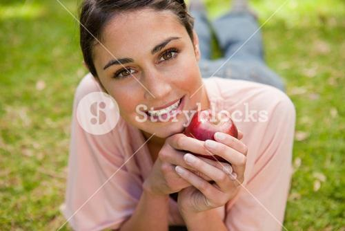 Woman looking ahead while holding an apple