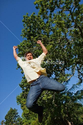 Man raising both of his arms and both of his legs as he jumps in celebration
