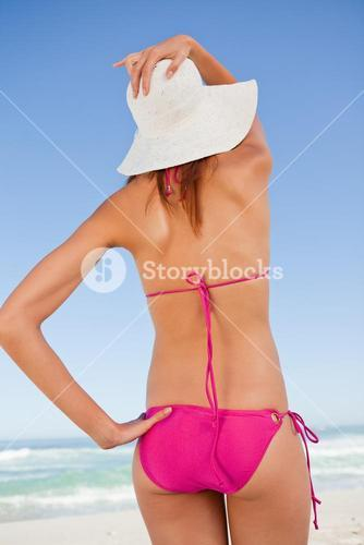 Back view of an attractive teenager in beachwear holding her straw hat