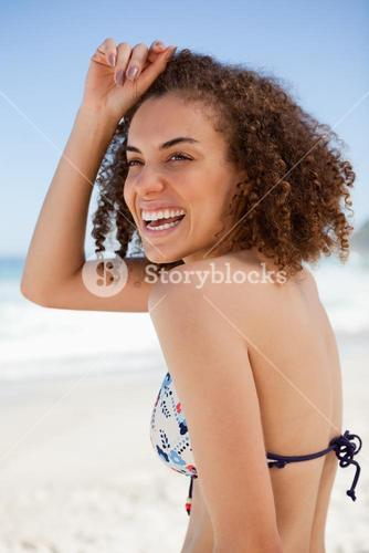 Smiling woman placing her hand on her forehead while standing on the beach