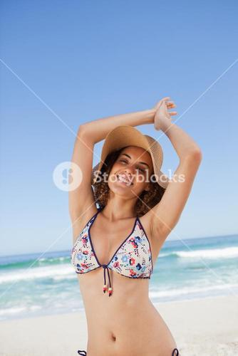 Young happy woman in beachwear joining her hands above her head