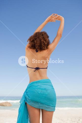 Rear view of a beautiful woman in beachwear raising her arms with hands crossed