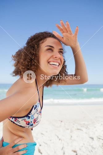 Happy young woman placing her hand on her forehead to look far away