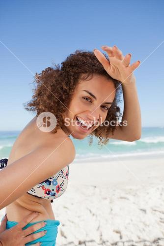 Young smiling woman placing her hand on her forehead to look at the camera