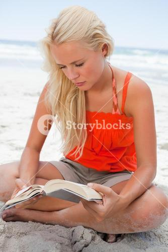 Young blonde woman sitting crosslegged while reading a book