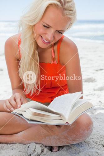 Young blonde woman reading a book while sitting crosslegged on the beach