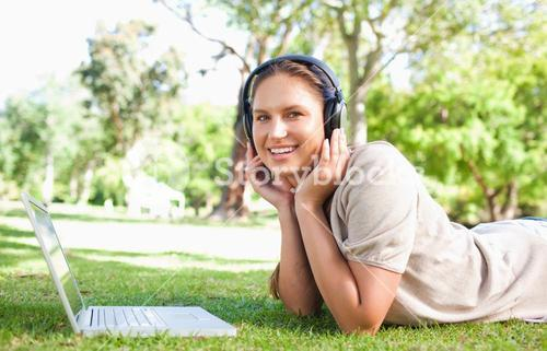 Woman with a laptop and headphones lying on the lawn