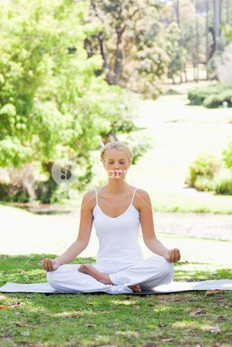 Woman sitting in a yoga position on the grass