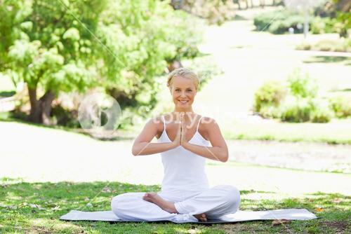 Smiling woman sitting in a yoga position on the lawn