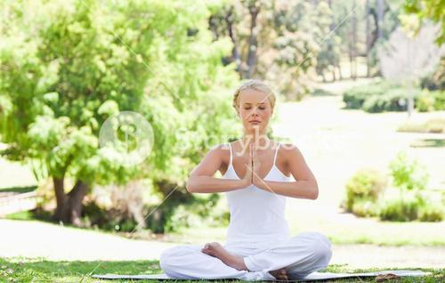 Woman in a yoga position sitting in the park