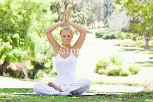 Woman sitting in a yoga position outdoors