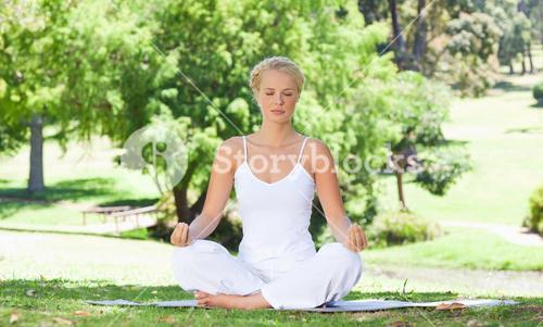 Woman sitting on the meadow in yoga position