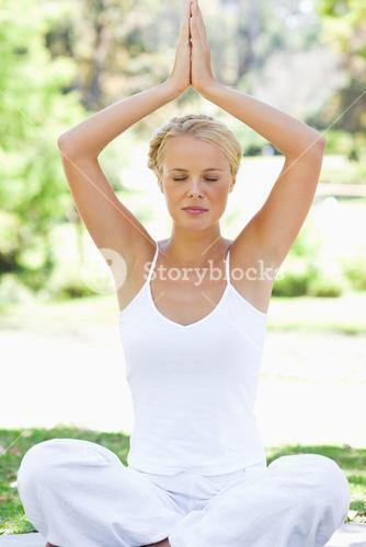 Relaxed woman in a yoga position on the meadow