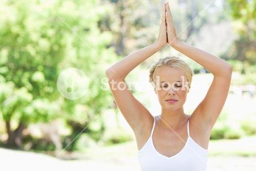 Relaxed woman in a yoga position in the park