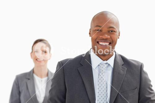 Smiling businessman with smiling businesswoman standing behind