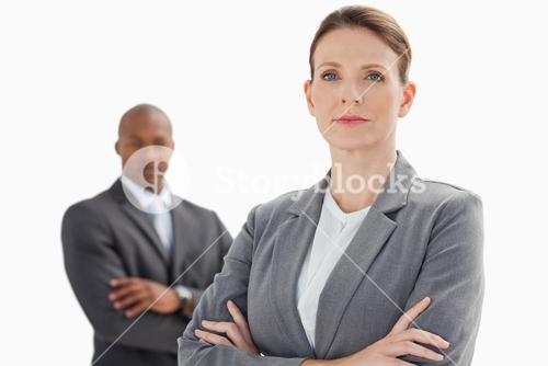 Businesswoman with folded arms in front of businessman with folded arms