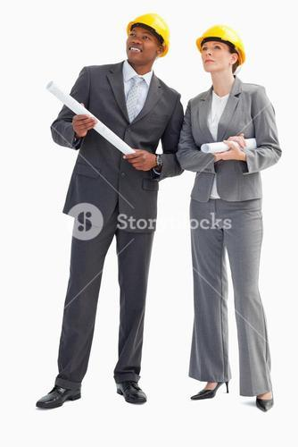 Businessman and a woman with notes and hard hats
