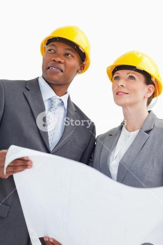 Smiling business people wearing hard hats are holding a paper