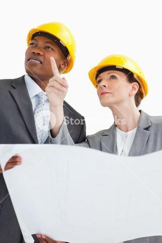 Business people wearing hard hats are talking