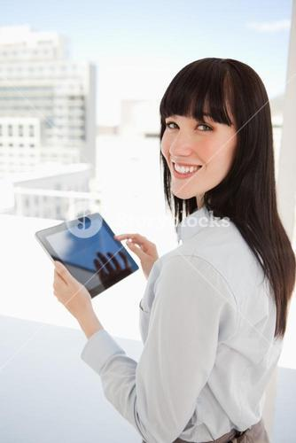 Woman looking into the camera as she holds a tablet pc in her hands