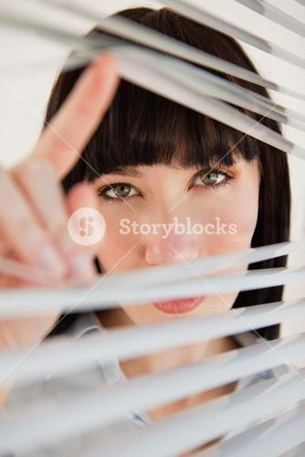 Woman looking through some blinds into the camera