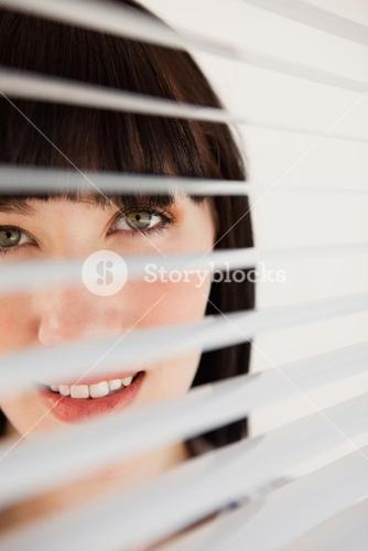 Woman looking forward through her blinds without moving them