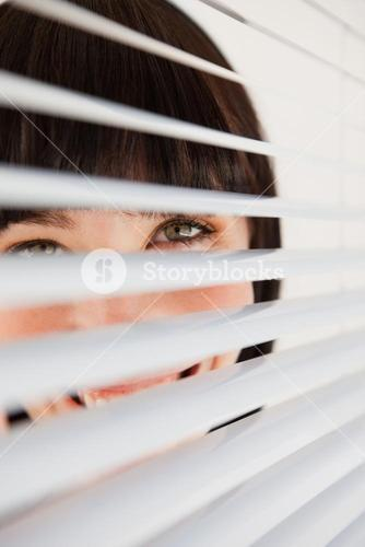 Smiling business woman looking through her blinds