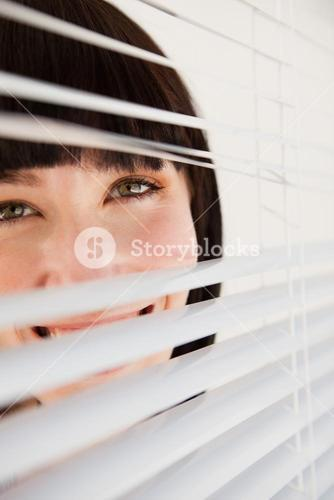 Woman looking through blinds she has opened slightly