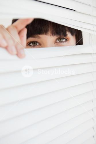 Closed set of blinds with open part opened by a woman