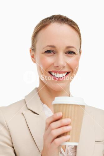Portrait of a woman in a suit holding a takeaway coffee