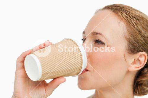 Close up of a woman in a suit drinking a takeaway coffee