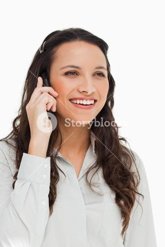 Brunette woman smiling while talking on the mobile phone