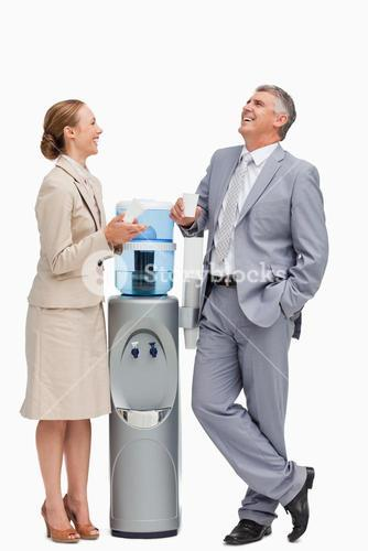 People in suit laughing next to the water dispenser