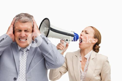 Businesswoman screaming with a megaphone at her colleague