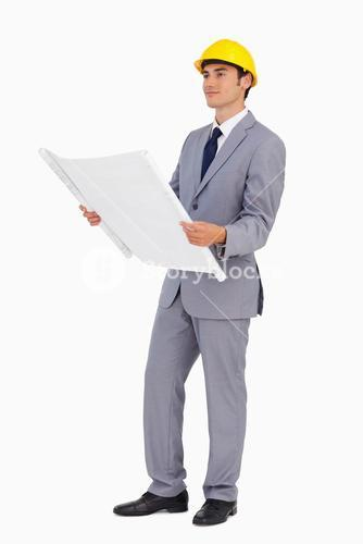 Goodlooking man in a suit with safety helmet and plans
