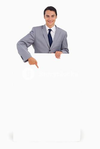 Goodlooking man holding and pointing at a big poster
