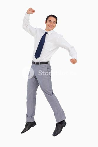 Businessman raising his arms and jumping