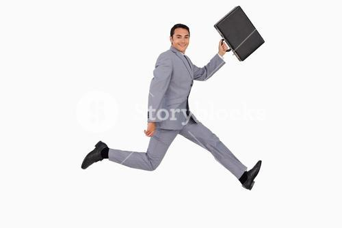 Portrait of a businessman running with a suitcase