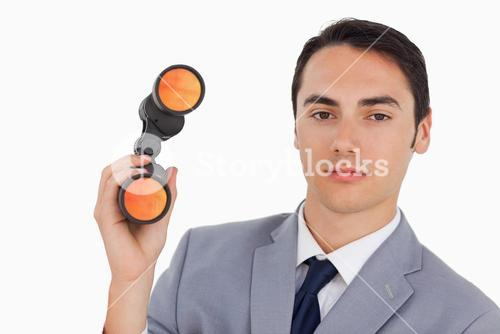 Close up of a handsome businessman with binoculars